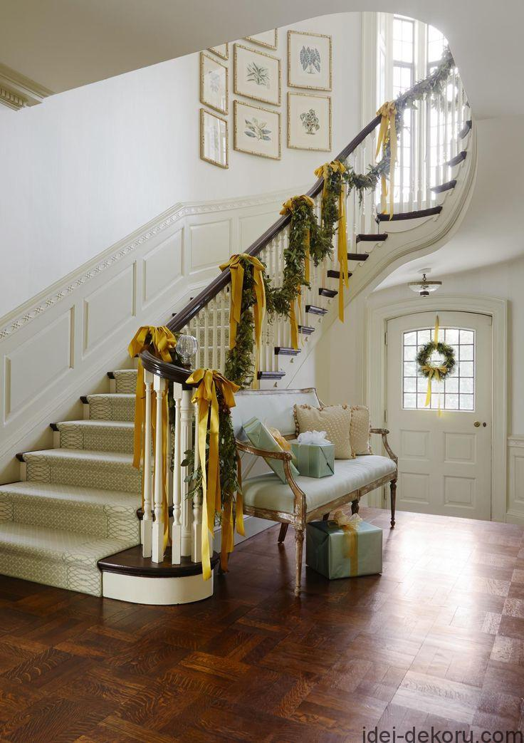 Garlands tied with gorgeous golden bows drape the banister in this gracious entryway, while wrapped gifts placed on the bench reference the light shades of blue found throughout the house.