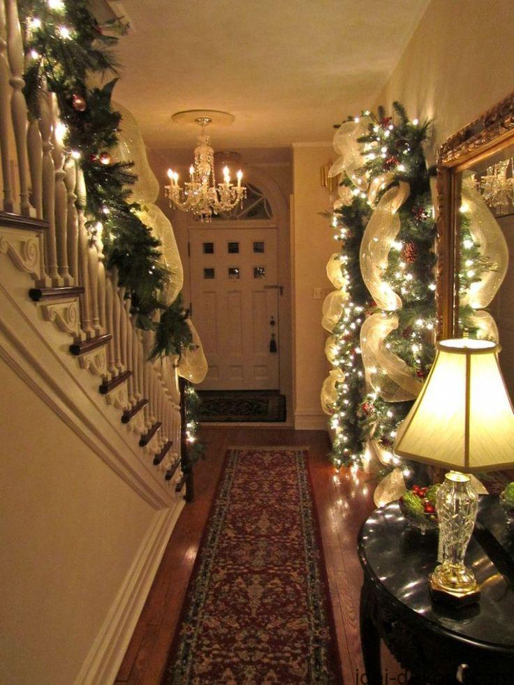 Awesome minimalist interior hallway design in cool Christmas decoration with trailing garland and beautiful lighting details.