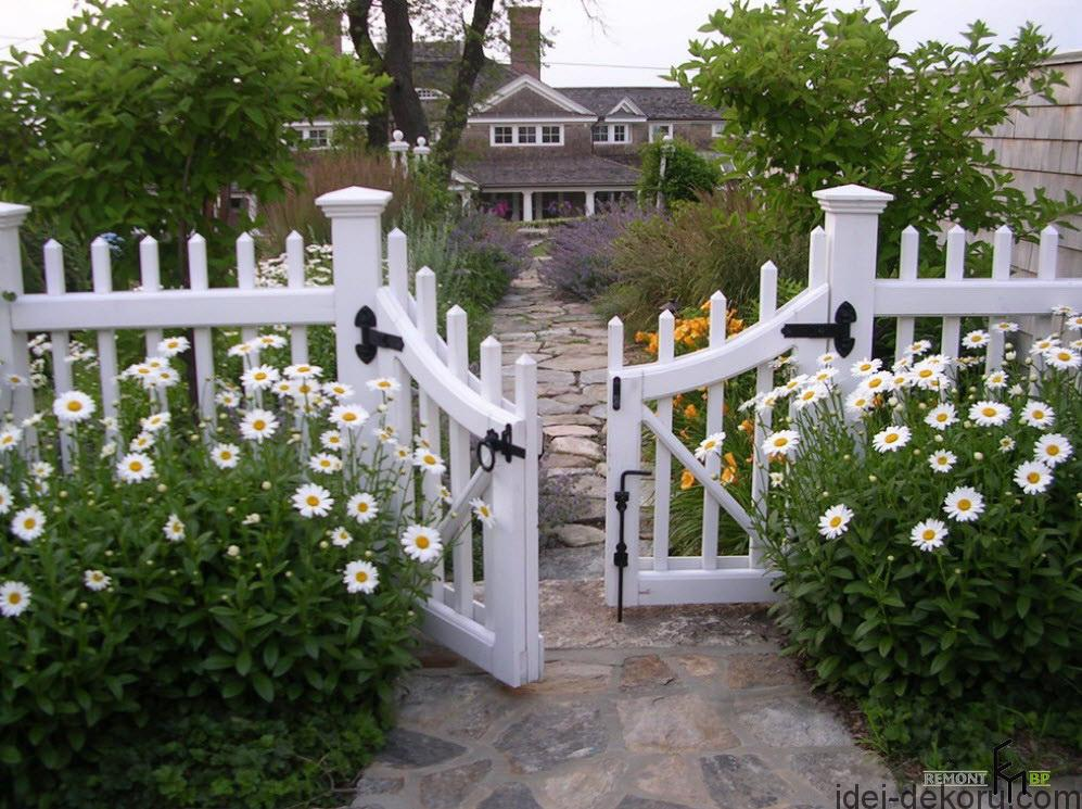a-stunning-picket-fencing-with-yellow-and-white-daisy-flower-also-fieldstone-paving-pathways-to-create-humble-atmosphere