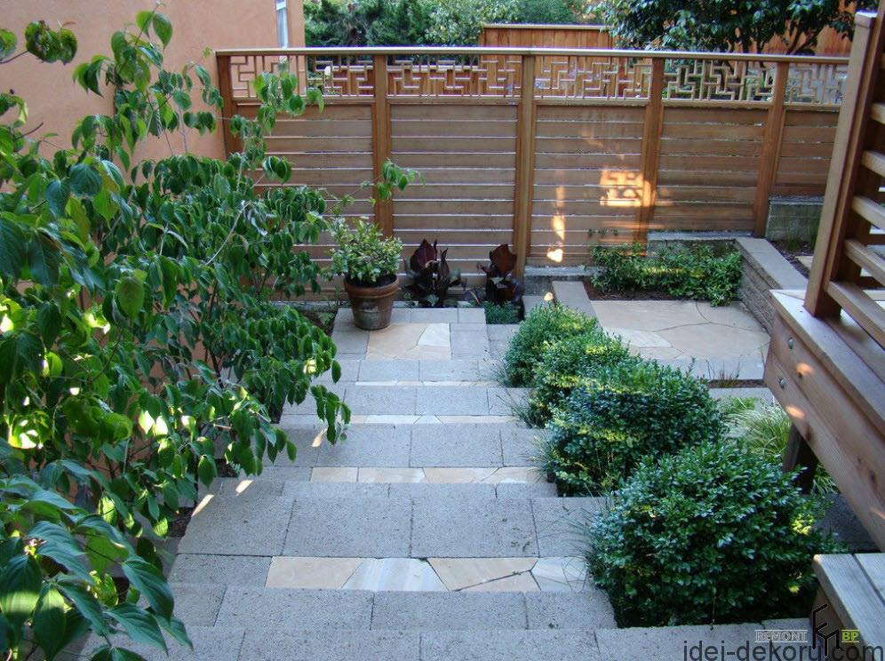 a-traditional-wooden-fencing-with-fieldstone-stairs-and-boxwood-shrubs-flank