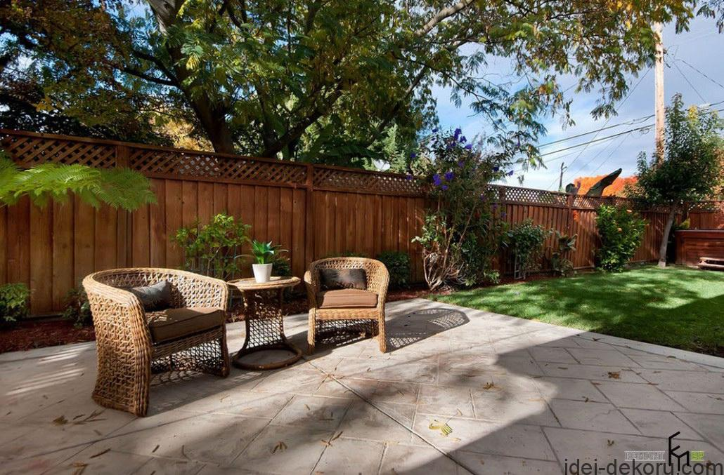an-ethnique-wooden-fencing-with-concrete-patio-and-simply-brown-wickery-armchairs-also-grassy-field