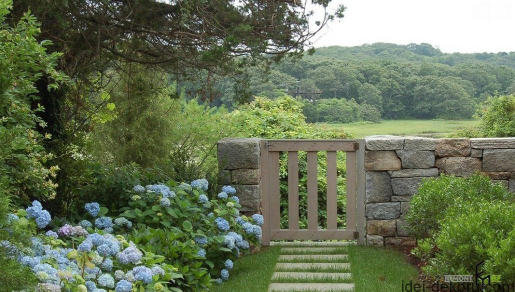 an-extraordinary-stony-fencing-with-wooden-combination-also-subtle-pathways-with-charming-blue-flower-and-great-forest-view