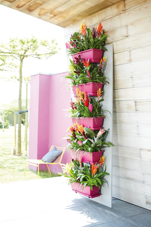 03-bright-pink-adds-a-pop-of-color-and-accents-vibrant-bromeliads-vertical-garden-homebnc