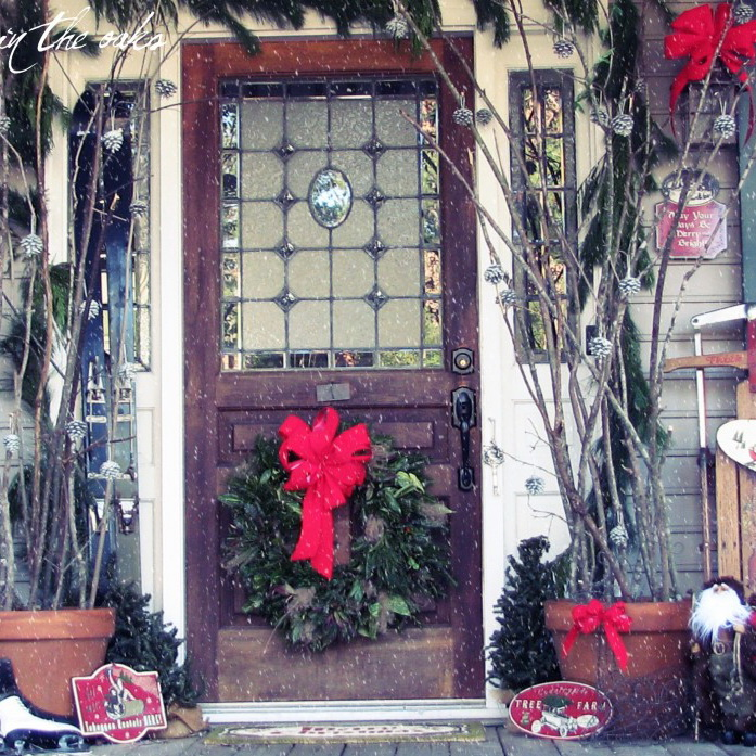 Fascinating Front Porch Decorating For Christmas By Green Circle With Red Ribbon Placed On The Brown Wooden Door Between Brown Pot With Sticks