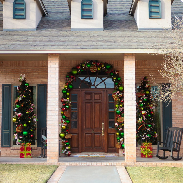 Mesmerezing Front Porch Decorating For Christmas By Colorfull Balls On The Brick Wall With Brown Wooden Door On The Middle Also Twin Christmas Tree