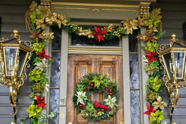 Remarkable Front Porch Decorating For Christmas By Colorful Flowers Around The Door Also Between Golden Wall Lamps Completed With Green Circle On The Brown Wooden Door