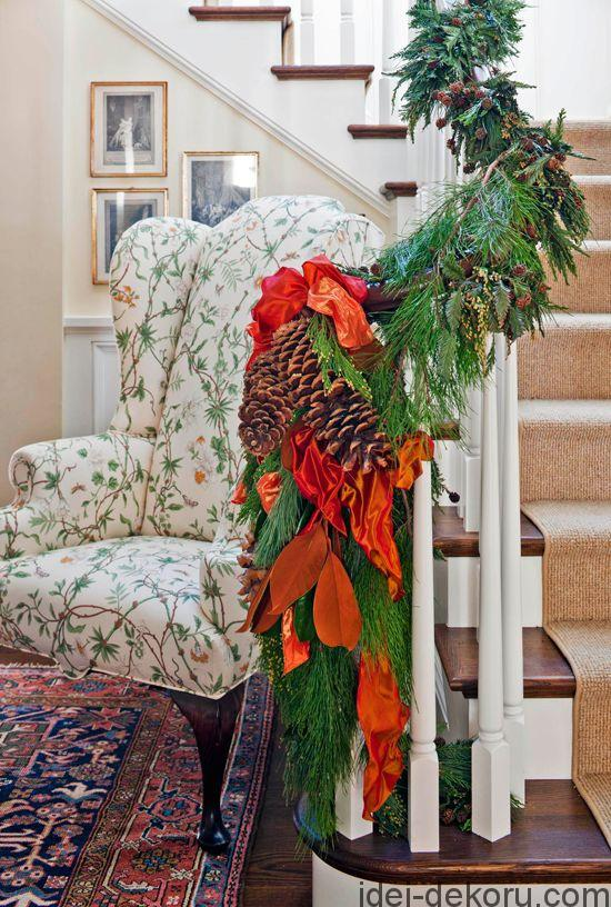 Large pinecones tied with bright ribbon cap off a banister garland. - Traditional Home ® / Photo: John Granen / Design: Elizabeth Hague