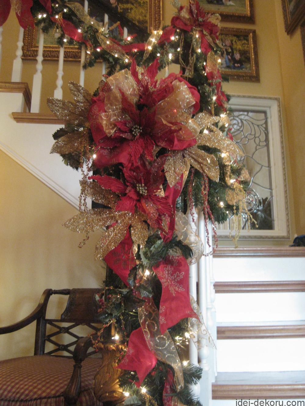 Gorgeous Christmas staircase with beautiful ribbon, poinsettias, glittered leaves, and hanging beaded berries.
