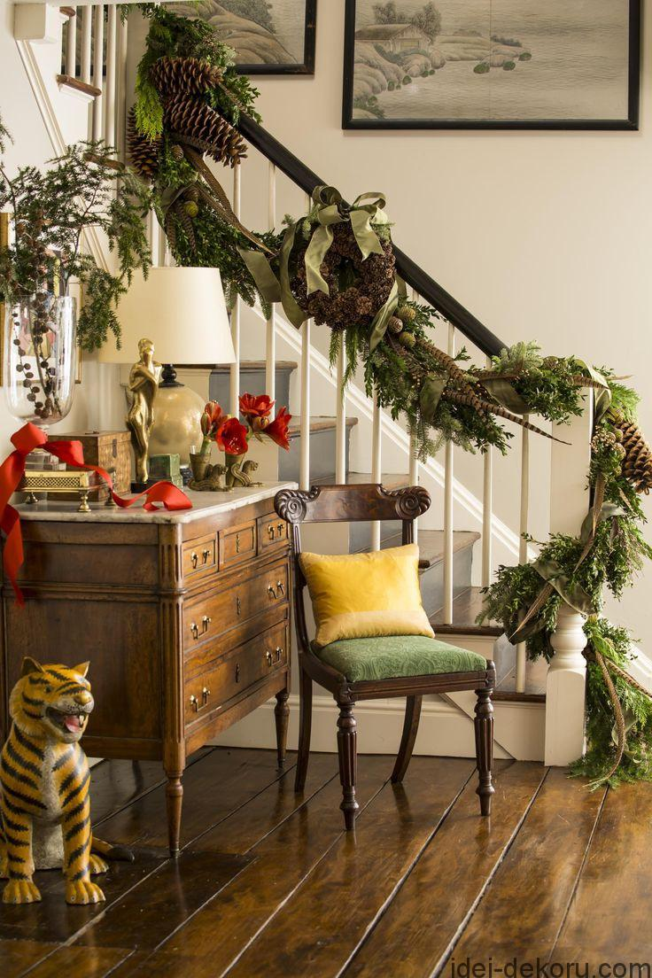 A garland winding up the stair rail is decked with fresh-cut greens, holly branches, giant pinecones, and pheasant feathers.