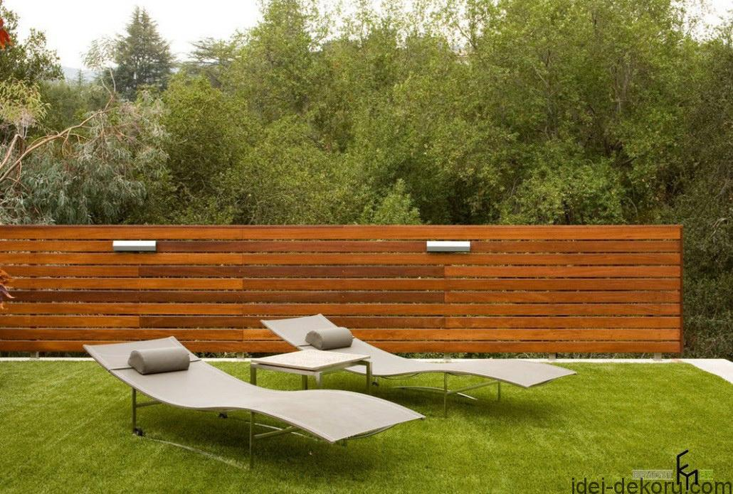 a-stunnig-striking-wooden-fencing-with-grassy-backyard-and-modern-easychairs-for-sunbathing