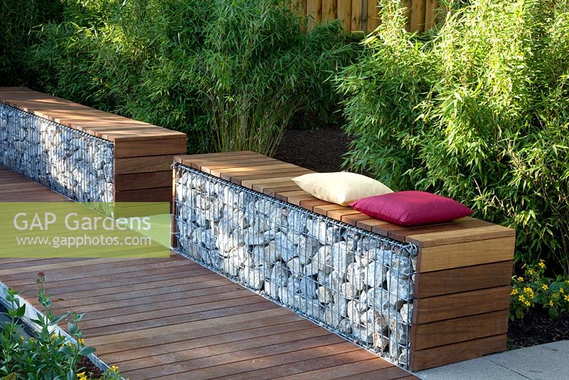 Bench made from wood and gabions backed by Fargesia murielae - Bamboo hedge